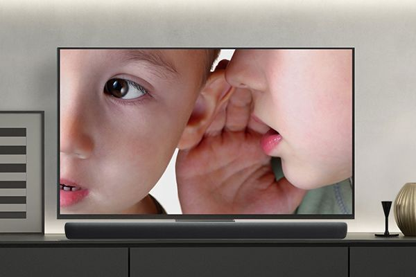 TV showing little boy whispering into the ear of another little boy