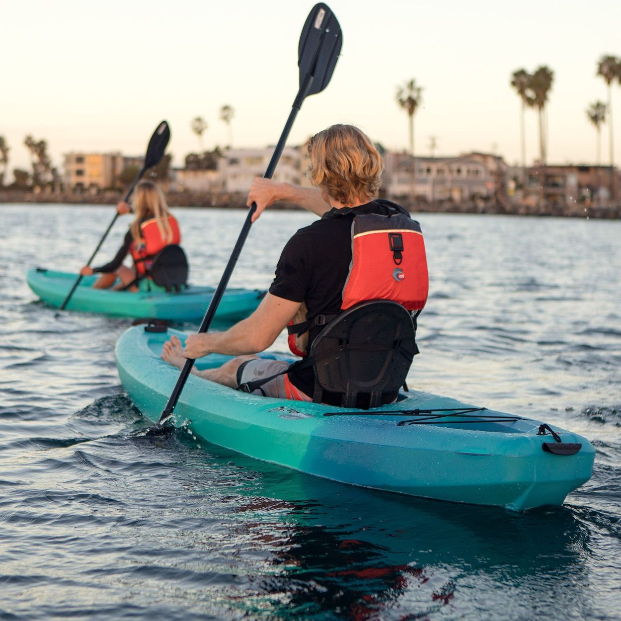 A man and a woman kayaking away from the camera with palm trees and buildings in the background past the water. Each person on the kayaks have life jackets that are red and black.