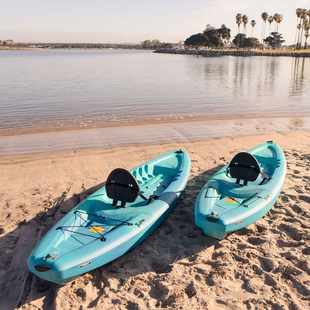 Two kayaks on a beach facing away from the camera and the water in the background with palm trees and other trees on an island in the far background.