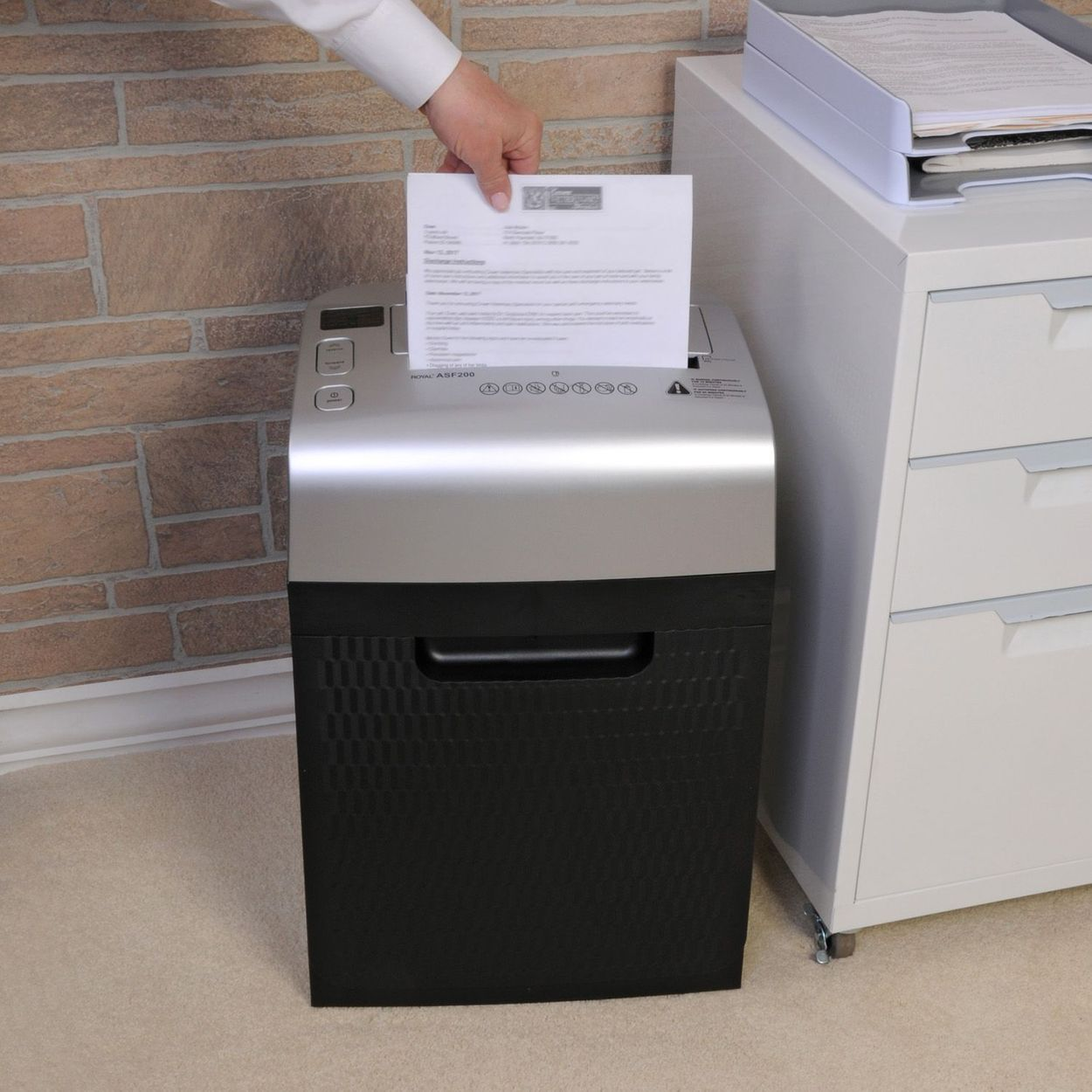 Lifestyle image of unit with hand feeding paper into slot