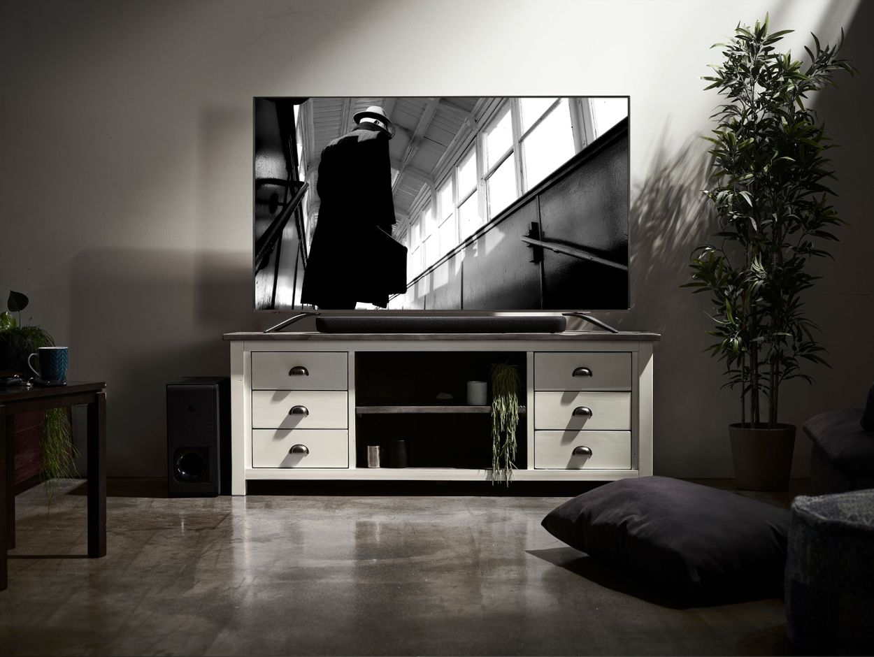 Sound bar on credenza in front of TV with movie on screen